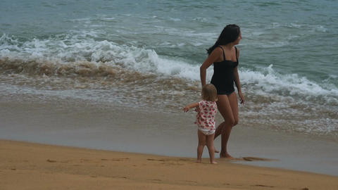Mother and daughter are running on the beach from ocean waves Footage