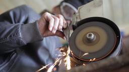 Senior man using grinder to sharpen a hatchet Footage
