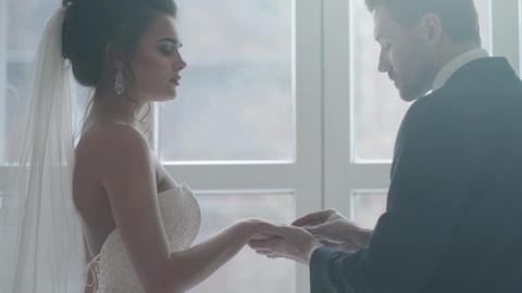 Groom putting ring on bride's finger Footage
