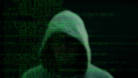 Man in hoodie points gun in background with scrolling hacker text Footage