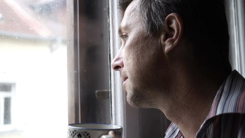 Man Looking Out Window Drinking Coffee Footage