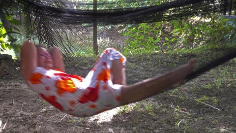 Little girl swinging in hammock in jungle Footage
