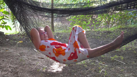 Little girl swinging in hammock in jungle Footage