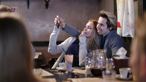 Hipster couple doing selfie with cellphone in cafe Live Action