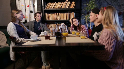 Happy young group of friends meeting in a cafe Live Action