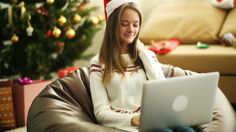 Pretty girl writing letter to Santa Claus on laptop at Christmas eve Footage