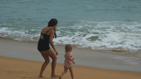 Mother and daughter are playing on the beach and having fun Footage