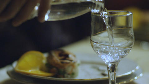 Closeup Mineral Water Pours from Glass Bottle to Small Goblet Footage