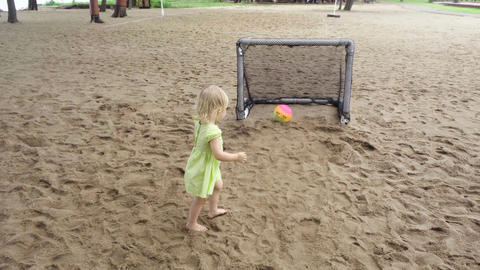 Pretty little girl stands near mini football gates and claps Footage