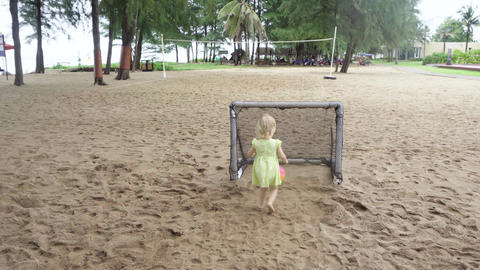 Pretty little girl stands near mini football gates and claps Stock Video Footage