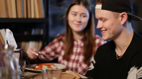 Cheerful teens enjoying meal sitting at cafe table Live Action