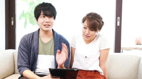 Couple using a mobile tablet device / pan Footage