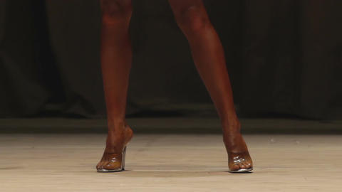 Long fit legs of professional female bodybuilder walking on stage, fitness show Footage