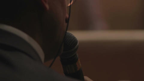 Man speaking into microphone, jury member announcing contest results, back view Footage