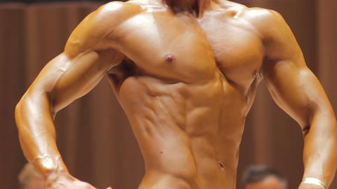Fitness bodybuilder demonstrating perfect masculine torso in relaxed side pose Live Action