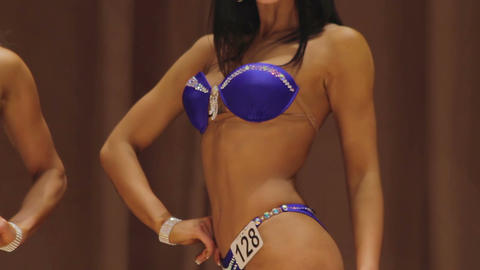 Sexy model demonstrating ideal feminine body in swimsuit at beauty contest Live Action