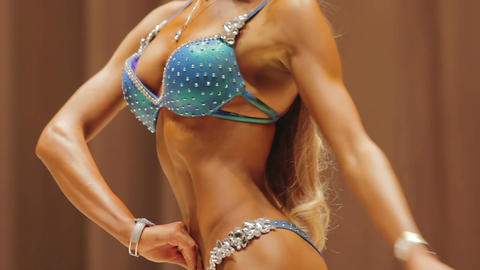 Blonde fitness model demonstrating sexy fit body at bodybuilding competition Live Action