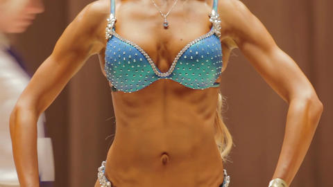 Female fitness competition participant demonstrating fit feminine body in bikini Live Action