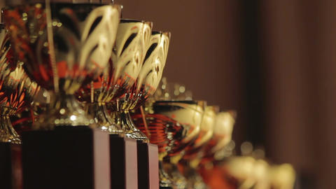 Lineup of golden cups for competition leaders, winner trophy, successful result Footage