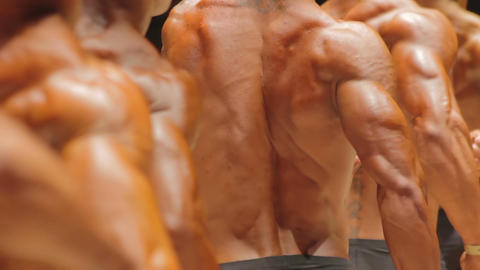 Men posing at competition to demonstrate massive muscular bodies, bodybuilding Live Action