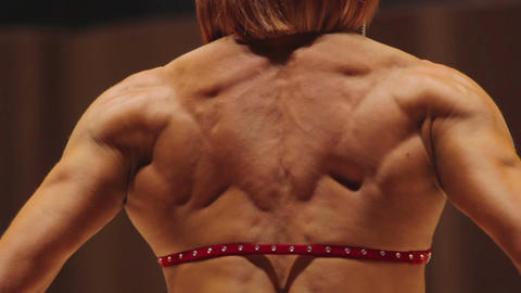 Female bodybuilder standing in rear lat and relaxed side poses to show muscles Footage