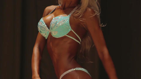 Hot fitness model with false breasts posing on catwalk in sparkling swimsuit Footage