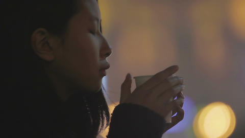 Offended depressed young woman drinking hot tea, sad woman holding back tears Footage