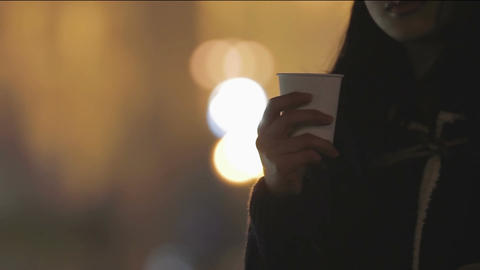 Beautiful young asian woman holding cup of hot drink, warming in cold weather Footage
