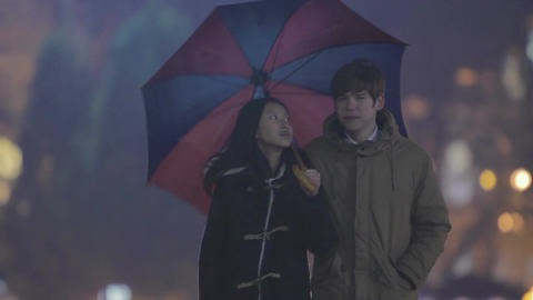 Teenagers having first date, couple walking in park with umbrella, relaxation Live Action