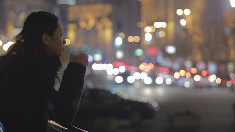 Pensive young woman drinking hot coffee on the street, night city, loneliness Footage