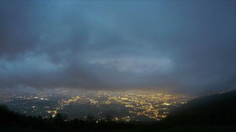 Timelapse of heavy mountain clouds, lights of night city lying below near sea Footage