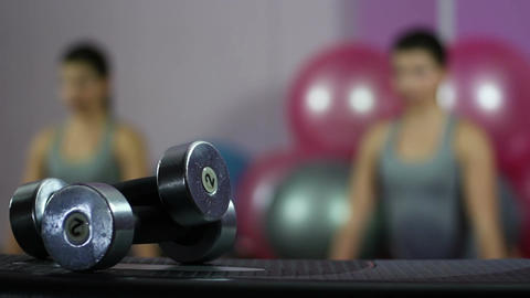 Flexible woman exercising in gym, close-up of dumbbells, healthy lifestyle Footage
