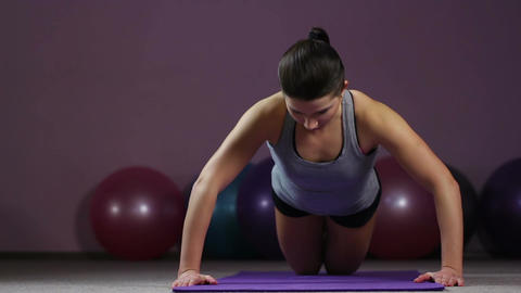 Young woman doing knee push-ups, working thoroughly to achieve fit body goal Footage