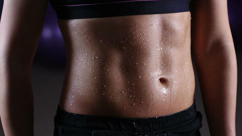 Water drops pouring down ideal flat tummy of sportive woman training in gym Live Action