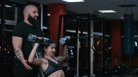 Male coach helping young woman with dumbbell exercise during workout in gym Footage