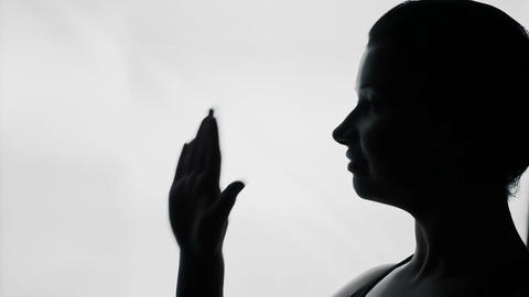 Young woman waving hand to say goodbye, farewell gesture, female silhouette Footage