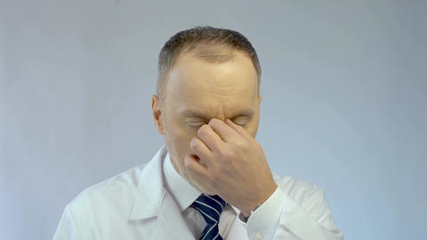 Overworked chief physician rubbing eyes, looking tired after busy working day Footage