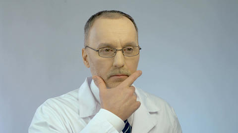 Serious male doctor touching face while thinking, finding solution, good idea Footage