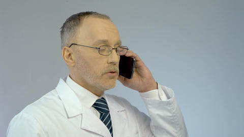 Doctor using mobile phone, dialing number, calling patient to arrange meeting Footage