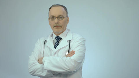 Successful confident doctor looking at camera with folded arms, clinic services Footage