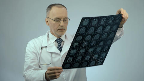 Neurosurgeon checking MRI brain image, looking at camera, health care services Footage