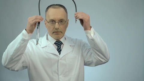 Professional therapist putting stethoscope around neck, ready to examine patient Footage