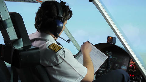Professional pilot filling out flight papers while flying airplane, profession Live Action