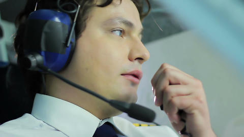 Handsome pilot talking to traffic controller while flying airliner, job duties Live Action
