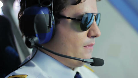 Young pilot wearing sunglasses and steering airliner, prestigious profession Live Action