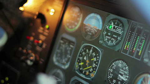 Flight control desk with changing indicators, pilot's hands on steering wheel Footage