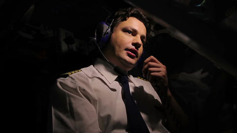 Concentrated aircrew commander steering plane and talking by walkie-talkie Footage