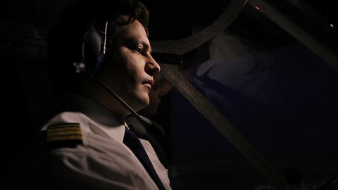 Male pilot in headset flying airliner and checking flight panel, aviation Live Action