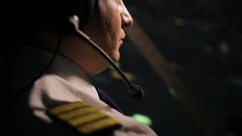 Attentive captain pilot in headset navigating huge airliner at night, job duties Footage