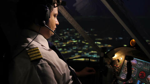 Professional aircrew commander navigating airplane above city at night time Footage